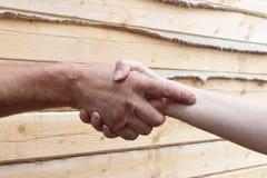 Las manos masculinas y femeninas bronceadas hacen el apretón de manos foto de archivo
