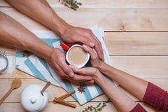 Las manos masculinas y femeninas están sosteniendo una taza entre ellos Imagen de archivo