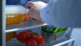 Las manos mayores del hombre abren la nueva puerta del refrigerador y toman una fruta anaranjada y el jugo fresco almacen de video