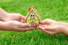 Las manos miman y un niño que sostiene una pequeña casa en un fondo fotografía de archivo libre de regalías
