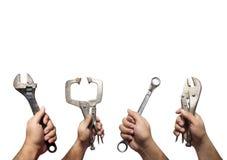 Las manos muchas del mecánico que sostenía los instrumentos, herramientas aislaron o Imagen de archivo