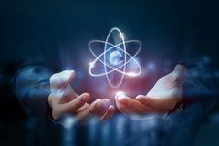 Las manos muestran el átomo fotografía de archivo