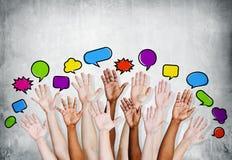 Las manos multiétnicas de la gente aumentadas con las burbujas del discurso Imágenes de archivo libres de regalías