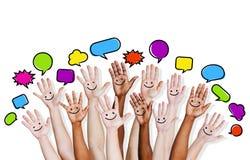 Las manos multiétnicas de la gente aumentadas con la burbuja del discurso Imagenes de archivo