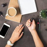 Las manos planas de la endecha de mujeres con la manicura colorida empiedran la superficie Fotos de archivo libres de regalías