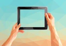 Las manos poligonales comunes que sostienen una tableta en el fondo les gusta a Imagen de archivo