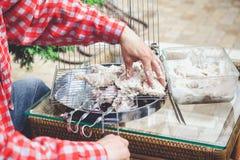 Las manos ponen pedazos de carne en parrilla de la barbacoa Fotografía de archivo libre de regalías