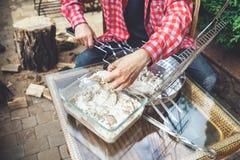 Las manos ponen pedazos de carne en parrilla de la barbacoa Imagen de archivo libre de regalías