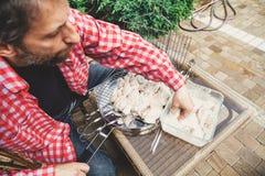 Las manos ponen pedazos de carne en parrilla de la barbacoa Fotos de archivo libres de regalías