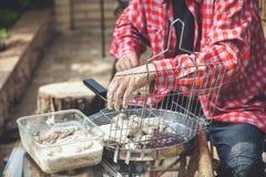 Las manos ponen pedazos de carne en parrilla de la barbacoa Fotografía de archivo