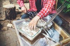 Las manos ponen pedazos de carne en parrilla de la barbacoa Foto de archivo