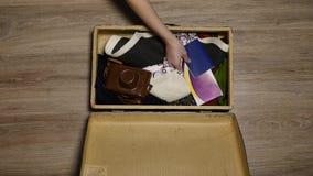 Las manos pusieron el pasaporte en maleta Mapa y pasaporte en la ropa Estación de las vacaciones La mujer consigue lista para el  almacen de video