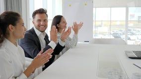 Las manos que aplauden en la cámara lenta, empleados de la unidad de negocio feliz aplauden en la oficina, colegas cerca del escr metrajes