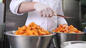 Las manos que el chef de repostería separó el azúcar en los albaricoques dan fruto, preparan el atasco en cocina industrial almacen de metraje de vídeo
