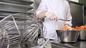 Las manos que el chef de repostería separó el azúcar en los albaricoques dan fruto, preparan el atasco en cocina industrial metrajes