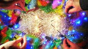 Las manos que encienden bengalas en el fondo con las plumas coloridas Visión superior metrajes