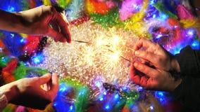 Las manos que encienden bengalas en el fondo con las plumas coloridas Visión superior almacen de metraje de vídeo