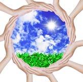 Las manos que forman un círculo forman en el cielo azul Fotos de archivo libres de regalías