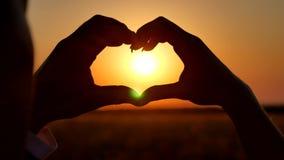 Las manos que forman un corazón forman con la silueta de la puesta del sol mano-forma para el Sun Manos que forman una forma del  almacen de video
