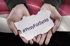 Las manos que llevan a cabo el texto de ruegan para Siria Imagen de archivo