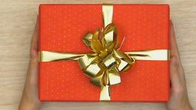 Las manos que ponen la caja de regalo en la tabla, presentan para la querida, celebración del día de fiesta almacen de metraje de vídeo