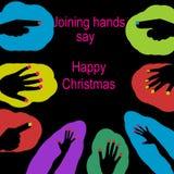 Las manos que se unen a dicen feliz Navidad Imagenes de archivo