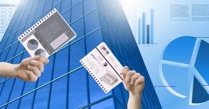 Las manos que sostienen documentos de la carta y el edificio alto con finanzas económicas trazan el fondo Imágenes de archivo libres de regalías