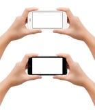 Las manos que sostienen smartphone adentro toman gesto de la foto Imágenes de archivo libres de regalías