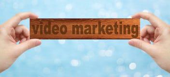 Las manos que sostienen una madera graban con el márketing video de la palabra Imagenes de archivo
