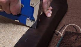 Las manos que tapizan el paricle suben usando la grapadora azul y el cuero marrón fotos de archivo libres de regalías