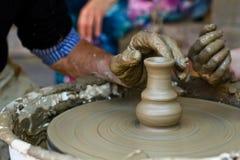 Las manos que trabajan en la cerámica ruedan, se cierran para arriba Imagenes de archivo