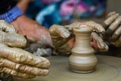 Las manos que trabajan en la cerámica ruedan, se cierran para arriba Imagen de archivo