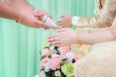 Las manos que vierten la bendición riegan en las bandas de la novia, boda tailandesa Nosotros Fotos de archivo