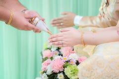 Las manos que vierten la bendición riegan en las bandas de la novia, boda tailandesa Nosotros Imagen de archivo