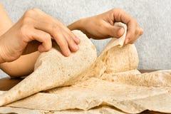 Las manos rasgan apagado un pedazo de pan Pita Imágenes de archivo libres de regalías