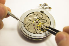 Las manos reparan un reloj viejo Imagen de archivo libre de regalías
