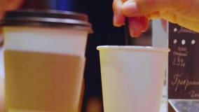 Las manos revuelven adentro la taza de bebida caliente para llevar Ci?rrese encima de tiro metrajes