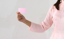 Las manos rosadas hermosas del vestido de la mujer que llevan a cabo un negocio rosado visitan la tarjeta Fotos de archivo libres de regalías