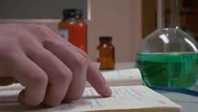 Las manos se abren y mirando algo en un diario, cuaderno manos de la escritura del científico en el cuaderno, manos del ` s de la almacen de video