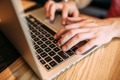 Las manos se cierran para arriba de los fingeres que mecanografían en el ordenador portátil, hombre en un café imagen de archivo