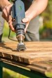 Las manos sirven con el disco giratorio eléctrico del metal del cepillo que enarena un pedazo de madera Imágenes de archivo libres de regalías