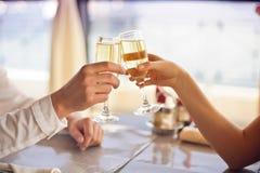 Las manos sirven y mujer con los vidrios de champán Fotografía de archivo