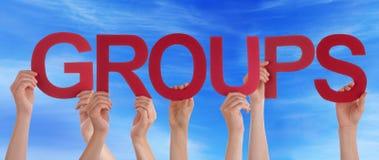 Las manos sostienen el cielo azul recto rojo de los grupos de palabra fotografía de archivo