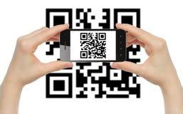 Las manos sostienen el teléfono elegante con código de QR Imagen de archivo libre de regalías