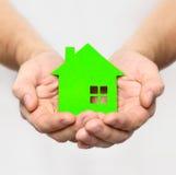 Las manos sostienen la casa verde imágenes de archivo libres de regalías