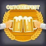 Las manos sostienen la taza de cerveza con el saludo de madera del fondo del icono del símbolo de Autumn Oktoberfest Celebration  Foto de archivo