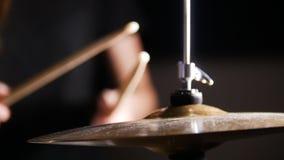 Las manos sostienen los palillos y golpean el platillo en un cuarto oscuro fotografía de archivo libre de regalías