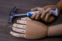 Las manos sostienen un martillo y clavos imagen de archivo