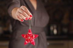 Las manos sostienen un ornamento rojo de la Navidad Abarcamiento del alcohol del Fotografía de archivo