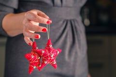 Las manos sostienen un ornamento rojo de la Navidad Abarcamiento del alcohol del Fotos de archivo libres de regalías
